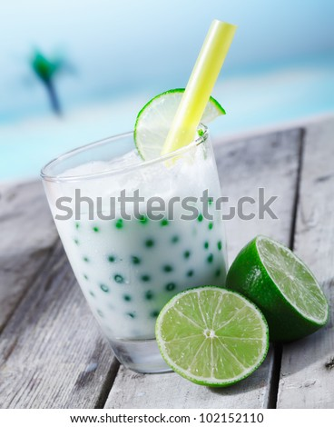 Fresh tapioka pearls tea with lime sirup standing in front of the beach on a wooden plate - stock photo