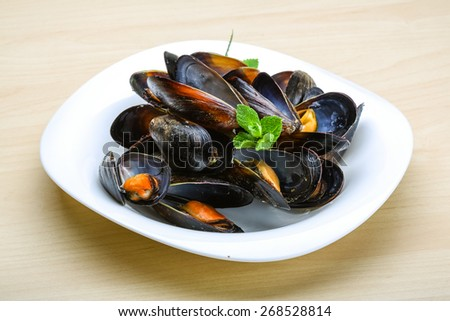 Fresh tasty Boiled mussels with herbs on wood background