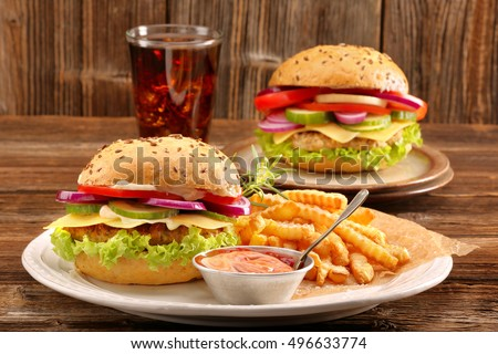 Fresh tasty burger with fries and drink on wooden table