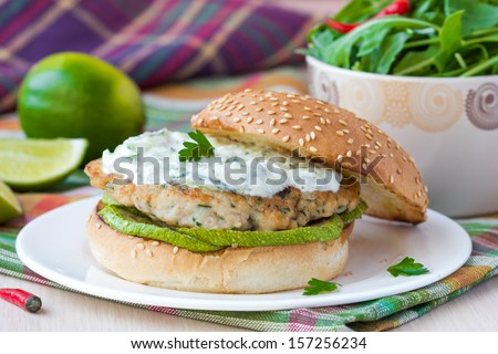Fresh, tasty chicken burger in the Greek style with zucchini and yogurt cucumber sauce tzatziki, lime, salad - stock photo