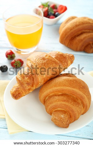Fresh tasty croissants with berries on wooden background - stock photo