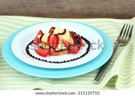 fresh tasty fruit salad on table, on wooden background - stock photo