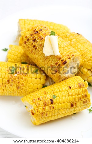 Fresh tasty grilled corn with butter on white plate - stock photo