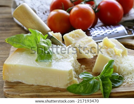 fresh tasty hard parmesan cheese on a wooden board - stock photo