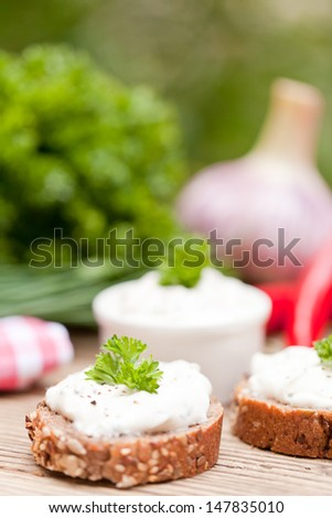 fresh tasty homemade cream cheese and herbs with bread on wooden table - stock photo