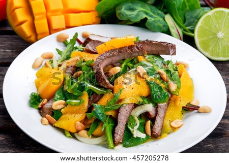 Fresh Tasty Mango, beef salad with vegetables and nuts. on wooden table