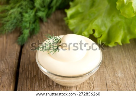 Fresh tasty mayonnaise sauce in bowl with vegetables (dill, lettuce) on rustic wooden background, close up, horizontal - stock photo
