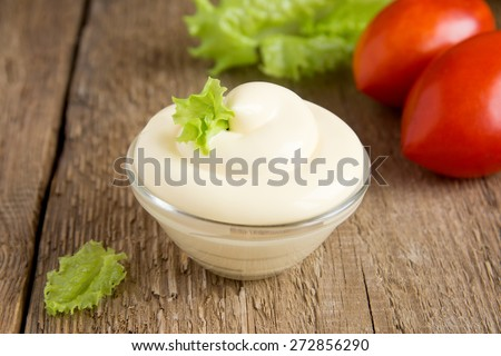 Fresh tasty mayonnaise sauce in bowl with vegetables (tomatoes, lettuce) on rustic wooden background, close up, horizontal - stock photo