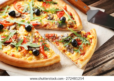 Fresh tasty pizza on brown wooden background - stock photo