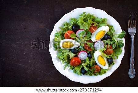 Fresh tasty salad with boiled eggs and vegetables in the plate,selective focus and blank space  - stock photo