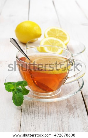 Fresh tea with lemon and mint in glass cup and cut lemon on rustic shabby white wooden table.