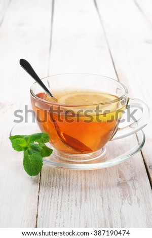 Fresh tea with lemon and mint in glass cup with saucer on rustic shabby white wooden table.