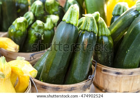 Fresh the farm zucchini in brown bushel baskets sitting on table at farmers market