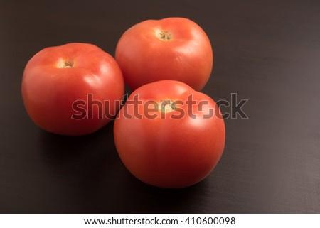 fresh three tomatoes on the black table - stock photo