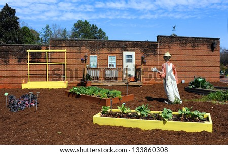 Fresh tilled soil and vegetable garden is guarded by scarecrow at the Riverbanks Zoo and Garden in Columbia, South Carolina. - stock photo