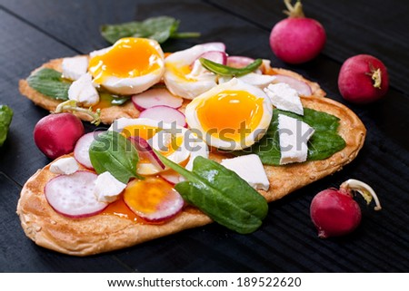 Fresh toast vegan sandwiches with soft-boiled egg, fresh radish, feta cheese and spinach on the black wooden table - stock photo
