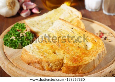 fresh toasted bread with garlic served on a wooden board.