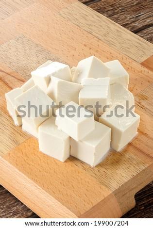 Fresh Tofu cubes on wooden cutting board. - stock photo