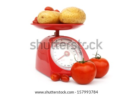 Fresh tomato and potato on kitchen scale  over white background - stock photo