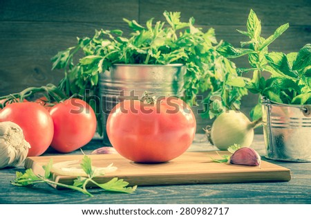 Fresh tomato and vegetables arranged on a wooden table