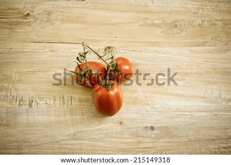 Fresh tomato branch at wooden background. Horizontal image with vintage filter. Objects at the central part of image
