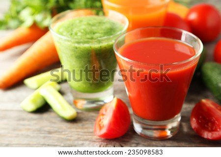 Fresh tomato, carrot and cucumber juice on grey wooden background