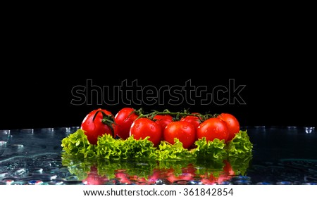 Fresh tomato cherry and green fresh salad with water drop splash on dark background Macro drops of water fall on the red cherry tomatoes and make splash - stock photo