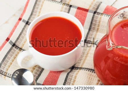 Fresh tomato juice in cup on wooden table. Selective focus.