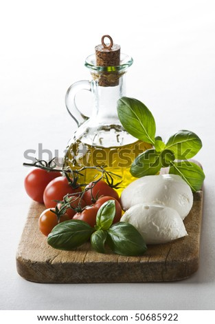 Fresh tomato, mozzarella, basil and olive oil close up - stock photo