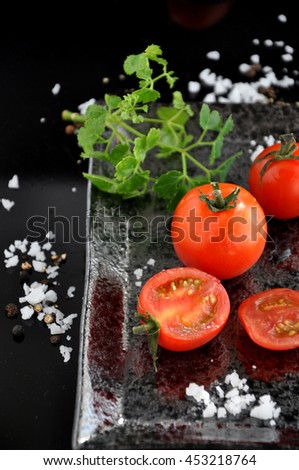 Fresh tomato on black tray with salt and pepper on background - stock photo