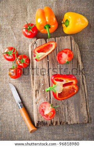 Fresh tomato, paprika, steel knife and vintage wooden cutting board on canvas tablecloth - stock photo