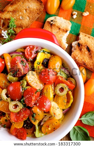 Fresh tomato salad with the addition of olives, onions and herbs  - stock photo