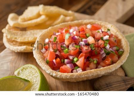 Fresh tomato salsa with serrano pepper, red onion, green onion, lime, and cilantro in a tortilla bowl. - stock photo