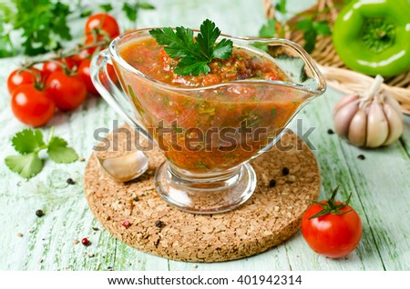 Fresh tomato sauce for meat on a wooden table. Sauce made from fresh tomatoes, paprika, garlic, herbs and hot peppers - stock photo