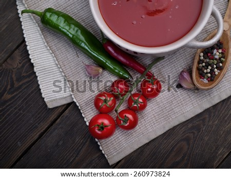 Fresh tomato soup in a white bowl and spices on dark wooden background - stock photo
