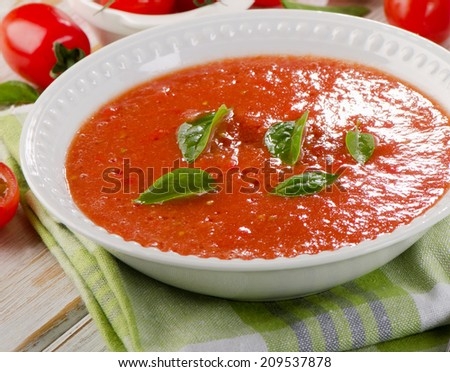 Fresh tomato soup in a white bowl on a wooden table - stock photo