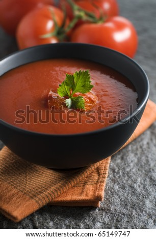 Fresh tomato soup in black bowl close up - stock photo
