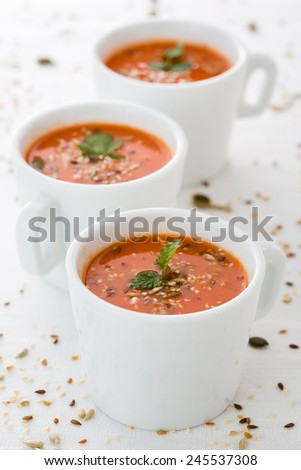 fresh tomato soup in cups with seeds and parsley. Vertical image. - stock photo