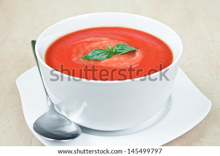 Fresh tomato soup with basil in a bowl