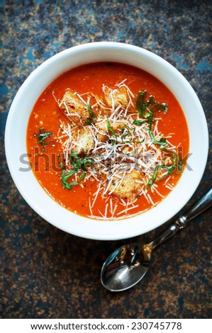 Fresh tomato soup with croutons, parmesan cheese and basil - stock photo