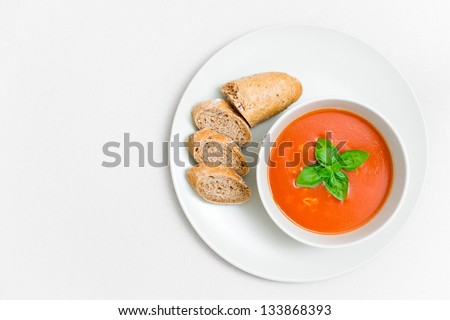 Fresh tomato soup with small bread and basil leaf on a plate with paper textured background