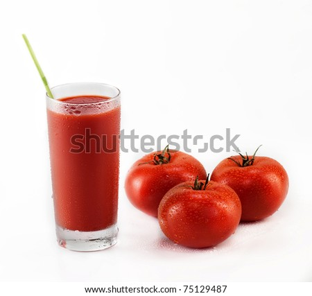 Fresh tomatoes and a glass full of tomato juice on white