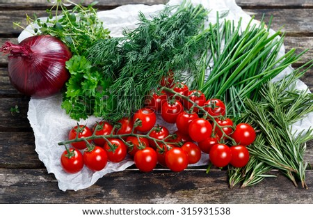 Fresh Tomatoes and Green Vegetables. Onion, Dill, Rosemary, Parsley, Chives and thyme. on old wooden table - stock photo