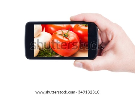 Fresh tomatoes and mushrooms on smartphone display or cellphone screen