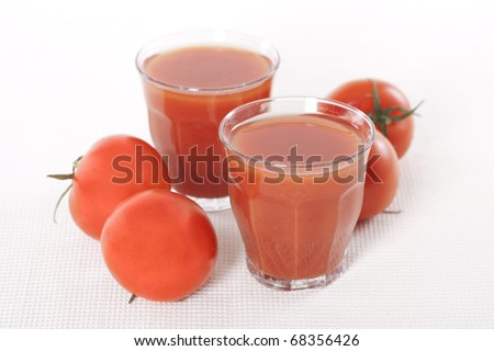 Fresh tomatoes and two glasses full of tomato juice