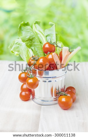 Fresh tomatoes and vegetables in little tin bucket on green background, wooden floor, shallow DOF - stock photo