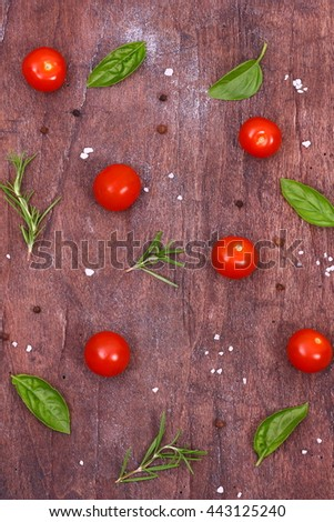 Fresh tomatoes, basil and rosemary on a wooden table. Seasonal background with vegetables and herbs. - stock photo
