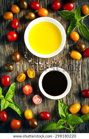 Fresh tomatoes, basil, olive oil and balsamic vinegar on wooden  - stock photo
