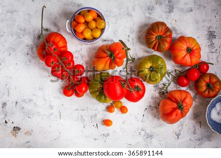 Fresh tomatoes. Colorful image with assorted colorful tomatoes on a stone table. Top view. Rustic style. - stock photo
