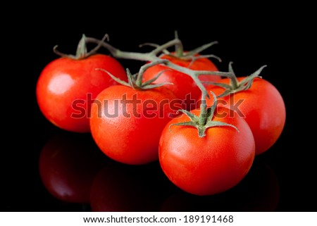 Fresh tomatoes composition. Vegetables photography taken on black surface.